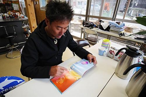 長明さんの写真をじっと見つめる越智カメラマンの胸中は……