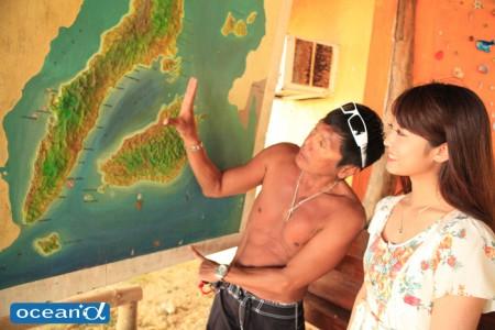 フロントにあるセブの地図でどこにいるのかを説明するBLUE CORALのヒロさん