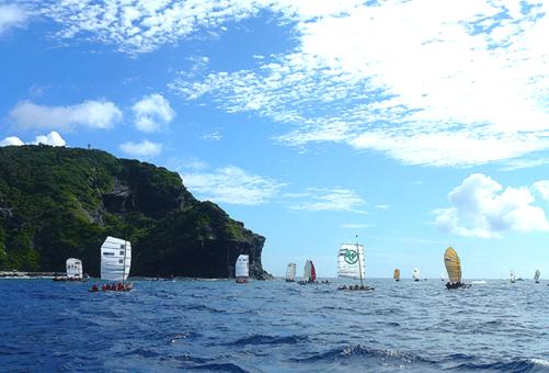 青空の下で帆を張る、座間味村のサバニ帆漕レース