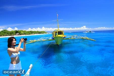 バリカサグ島の青い海とフォト派ダイバー(撮影:越智隆治)