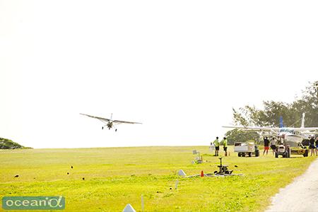 緑の芝生の滑走路にセスナで着陸
