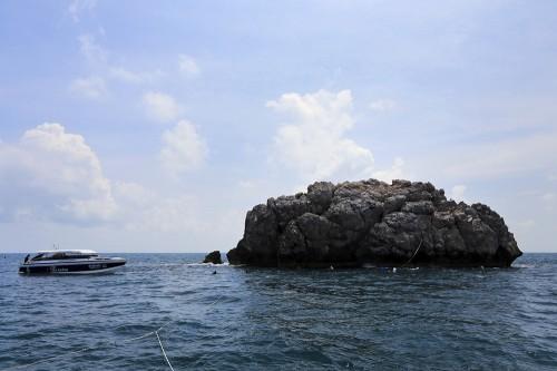 「セイルロック」の上部は海面に突き出ている。この岩礁の周りを潜る。一緒に写っているのはスピードボート。