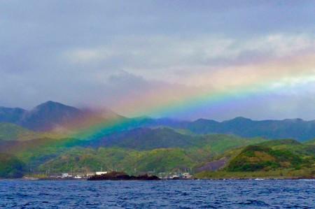 雨雲が去ると、海に迫る山並みに虹がかかった