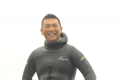 笑いながら遠くを見ているMOSS DIVERSオーナーガイドの森敬太さん