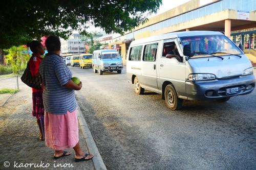 バスを待つ人々。車のナンバープレートに乗合バスを示す「B」の文字がある
