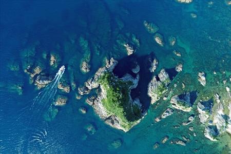 空から見たジオパークの観光名所、菜種五島。波の浸食でできた洞窟や島の周囲もダイビングポイント