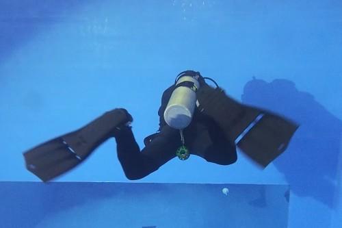 足を開脚しながらフィンを引き上げる