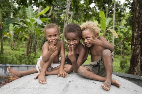第二次世界大戦の記念碑の上で遊ぶラバウルの地元の子どもたち。自然の中、裸足で元気に遊んでいた
