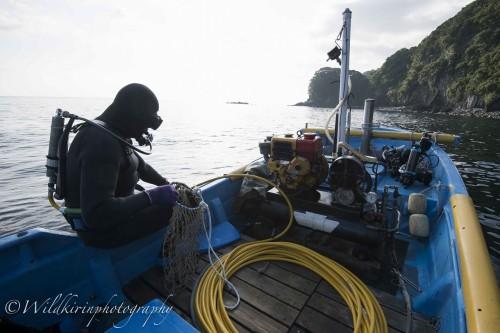 代々受け継がれているディーゼル製のコンプレッサーを始動させて潜水に向かう前の様子